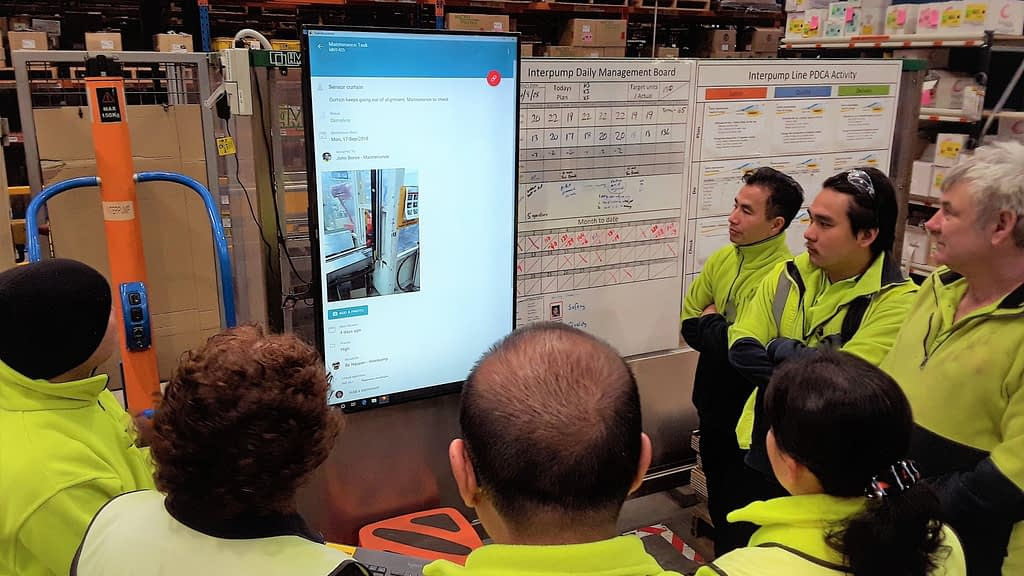 A shiftly tiered meeting in a manufacturing site, with a digital primary visual display and whiteboards.